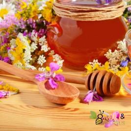 Cuillère à miel liquide en bois entouré de fleurs de printemps